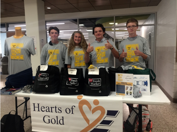 Kole+Butterer+%2719%2C+Hannah+Stuursma+%2718%2C+Andy+McCulloch+%2719%2C+and+Ryan+Smith+%2719+selling+Hearts+of+Gold+t-shirts+during+lunch.+