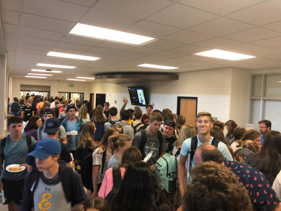 A crowd of students in the hallway next to the cafeteria wait patiently to receive their free food during fourth hour lunch.