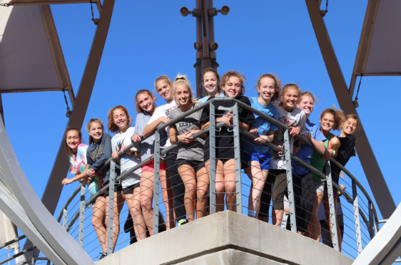 The girls cross country state team poses for a photo in Gaslight. These 14 girls are training for the November 3 race.