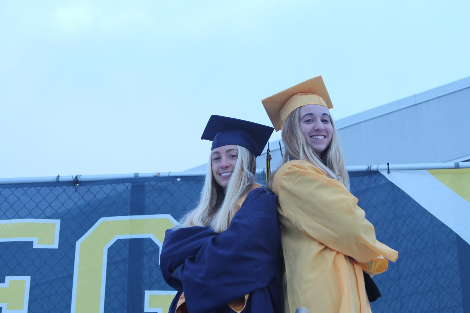 Audrey Whiteside '19 and Sloane Teske '19 show off the girls' traditional gold attire and the navy cap and gown for this spring.