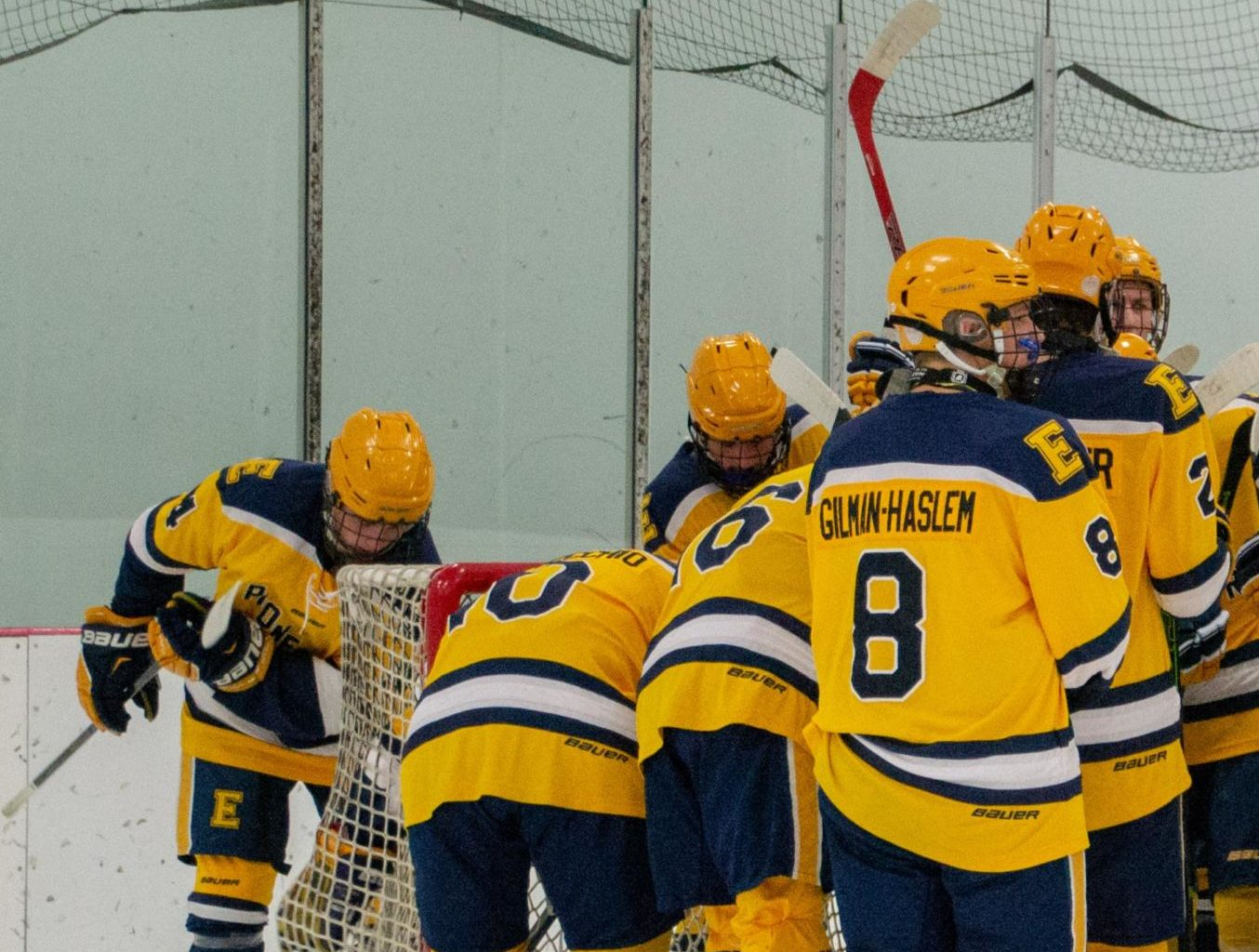 The boys hockey team gathers in a huddle at Patterson Ice Center during their first game of the season against Jenison high school.