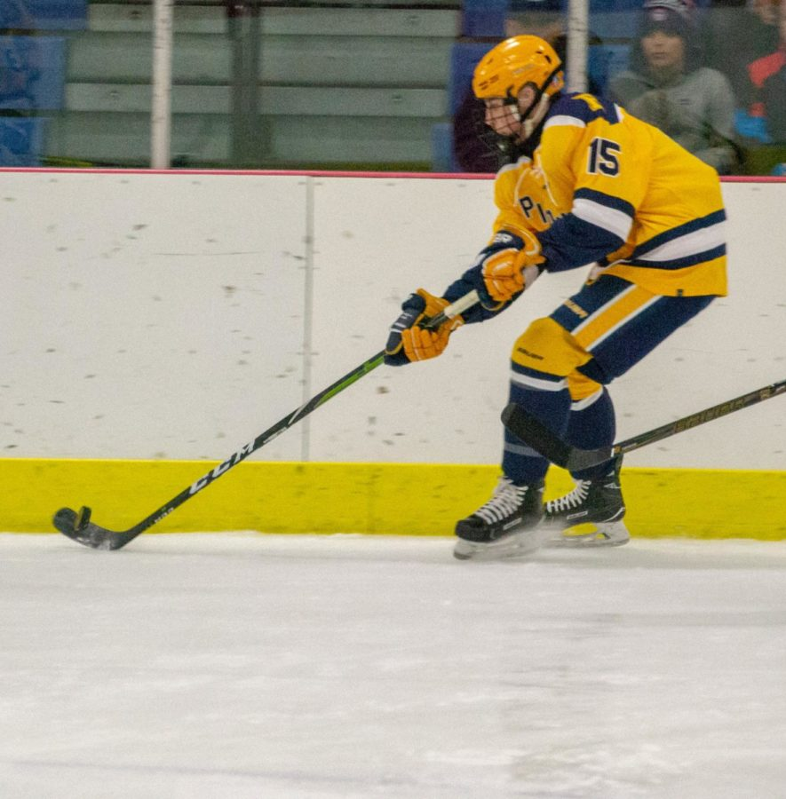 Forward Edward Albert '19 persistently keeps control of the puck as he skates toward the goal.