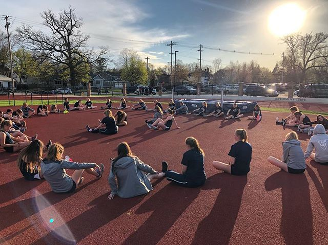 The+track+and+field+team+gathers+together+for+stretching+after+practice.