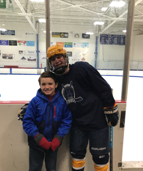 Nathan Milanowski '21 with Ayden at a East Hockey game.