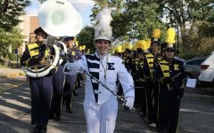Drum Major Rotem Andegeko 22 leads the marching band to the field.