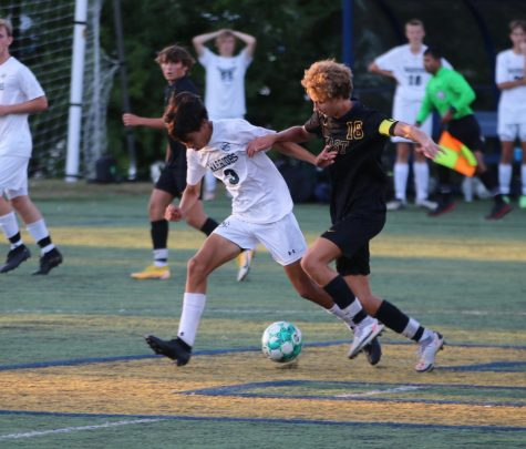Jonah Bishop 22 fights off a challenge from an opposing defender.