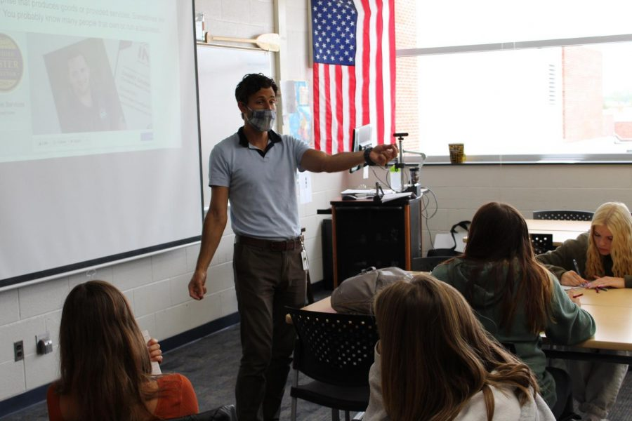 Social studies teacher Adam Horos instructs his economics class wearing his required mask