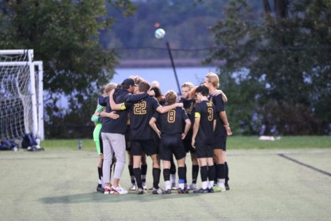 The soccer team huddles before the start of a game at Memorial Field